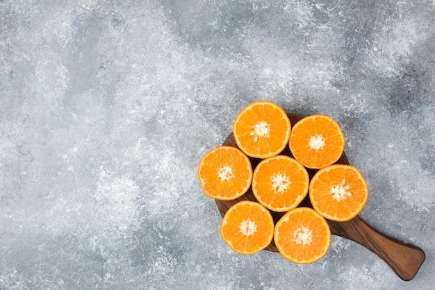 Деревянная доска сочных ломтиков апельсина на каменном столе.