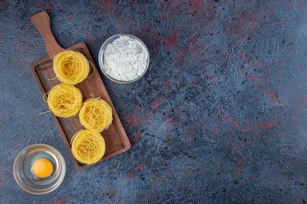 Деревянная доска сырых сухих макаронных изделий гнезда с мукой и сырым яйцом на темном фоне.