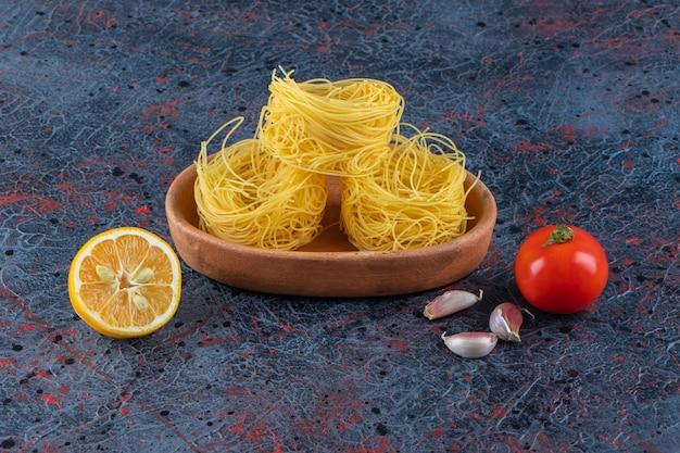Деревянная доска сырых сухих макаронных изделий гнезда с лимоном и свежими красными помидорами на темной поверхности.
