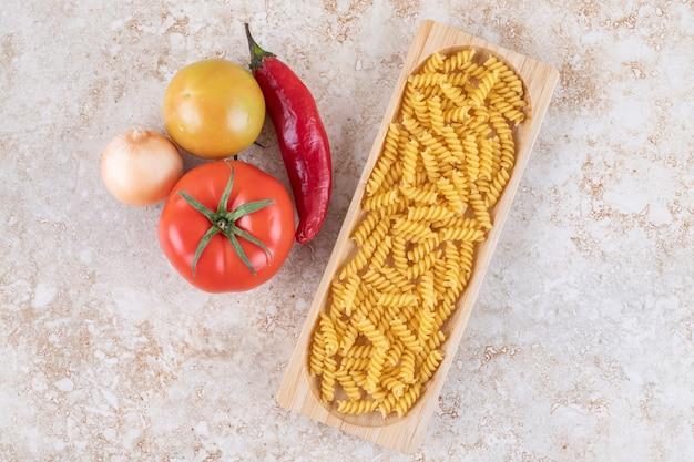生のスパイラルマカロニと野菜の木板