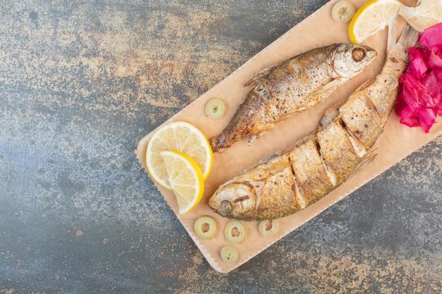 레몬과 양배추와 얇게 썬 생선의 나무 보드. 고품질 사진