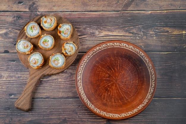 새우, 아보카도, 치즈, 오믈렛 빵가루가 곁들여 진 나무 스시 보드.