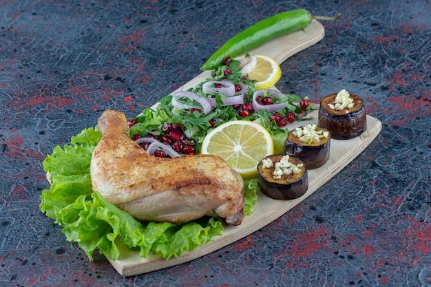 大理石の表面に美味しい料理が飾られた木の板。