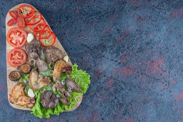Деревянная доска с вкусной едой на мраморной поверхности