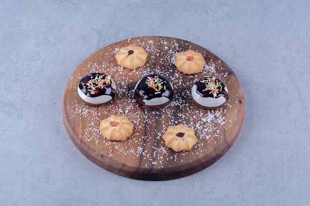 チョコレートシロップとさまざまな甘いクッキーが付いている木の板。