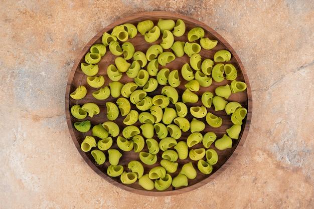 緑の準備されていないマカロニと木の板