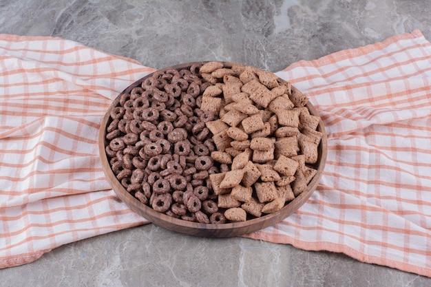 ヘルシーなチョコレートシリアルリングとチョコレートパッドコーンフレークが付いた木の板。