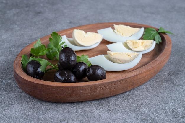 オリーブとゆで卵が入った木の板。高品質の写真