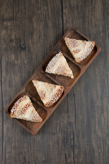 木製のテーブルの上においしいケーキのかけらが付いている木の板。