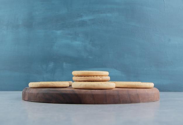 甘い丸いクッキーが付いている木の板。