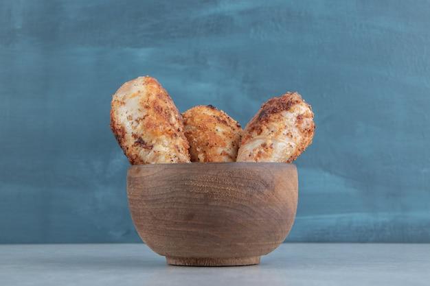 구운 닭다리 고기가 가득한 나무 그릇.
