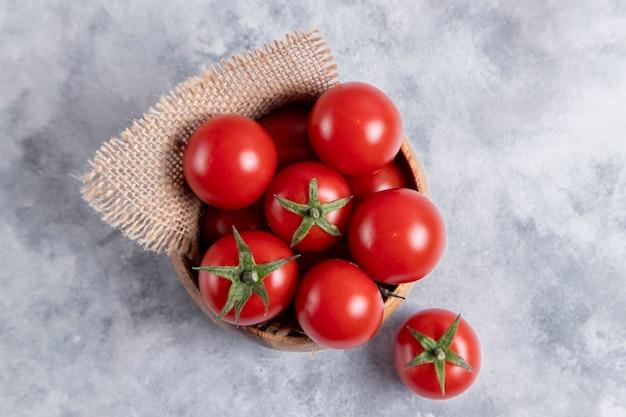 Деревянная миска, полная свежих сочных красных помидоров, помещенная на каменный стол. фото высокого качества