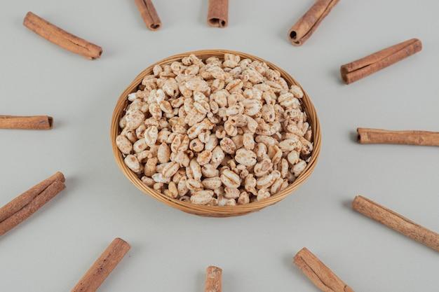 계피 스틱과 함께 건강한 곡물로 가득한 나무 그릇.