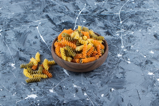 Деревянная миска, полная разноцветных макарон на серой поверхности.