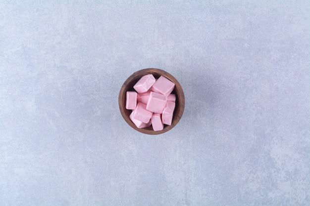 Деревянная миска, полная розовой сладкой кондитерской пастилы.