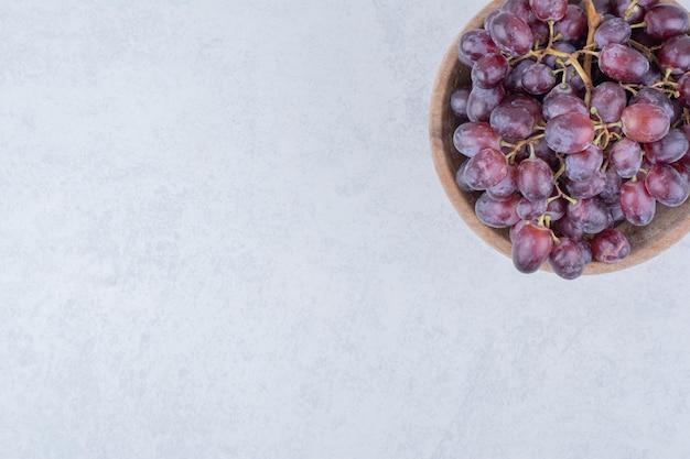 白い背景の上の紫色のブドウでいっぱいの木製のボウル。高品質の写真