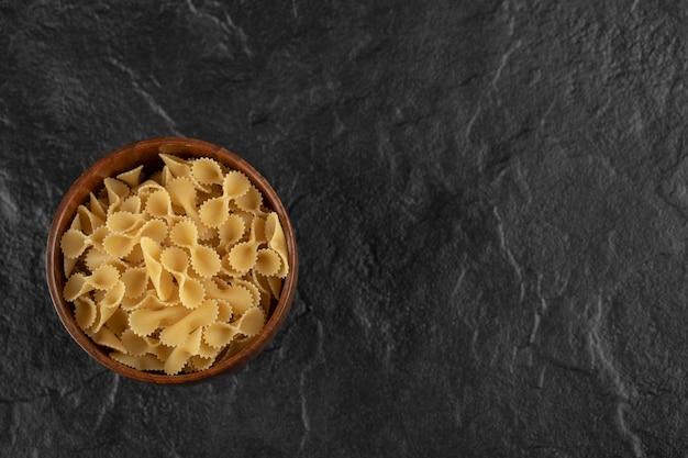 生のファルファッレトンデマカロニがいっぱい入った木製のボウル。
