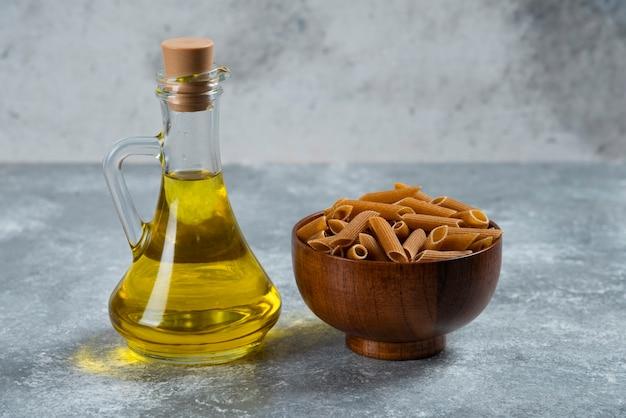 Деревянная миска, полная макарон из сырого зерна и стеклянная бутылка масла.
