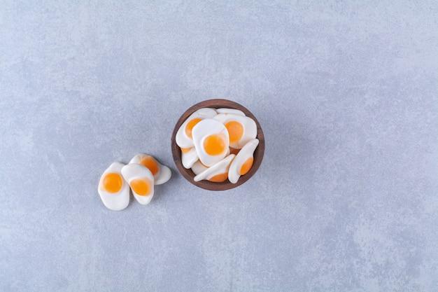 회색 배경에 달콤한 젤리 프라이드 계란이 가득한 나무 그릇. 고품질 사진