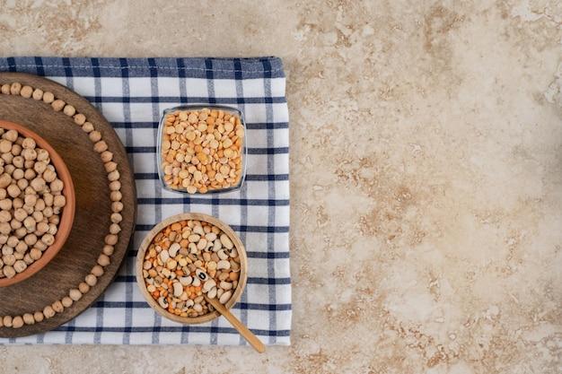 준비되지 않은 완두콩과 향신료와 콩이 가득한 나무 그릇