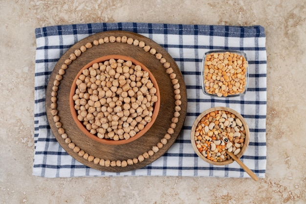 Деревянная миска, полная неподготовленного гороха со специями и фасолью.
