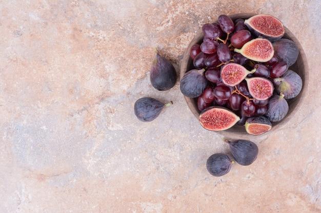 Деревянная миска с ягодами кизила и фиолетовым инжиром.