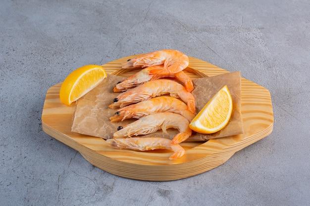 Деревянная миска вкусных креветок с нарезанным лимоном на каменном фоне.