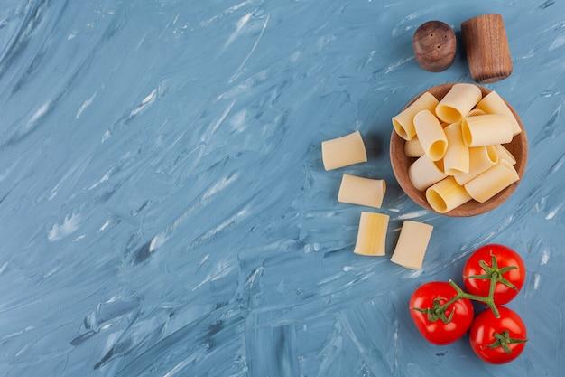 青いテーブルの上に新鮮な赤いトマトとスパイスが入った乾燥生チューブパスタの木製ボウル。