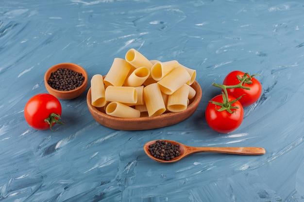 青いテーブルの上に新鮮な赤いトマトとスパイスが入ったドライ生チューブパスタの木製ボウル。