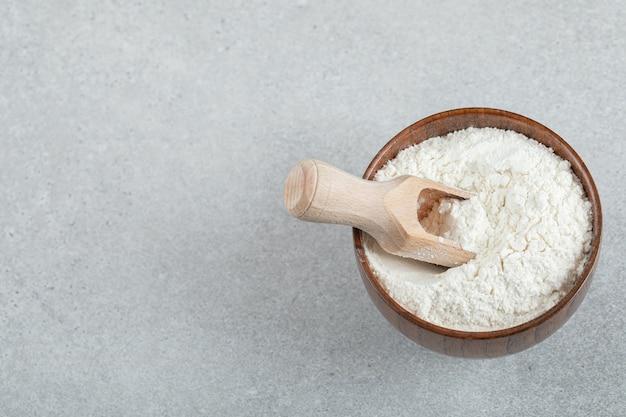 小麦粉と木のスプーンの木のボウル。