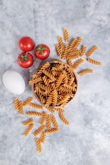 Деревянная миска итальянской сырой сухой пасты fusilli rigate с помидорами. фото высокого качества