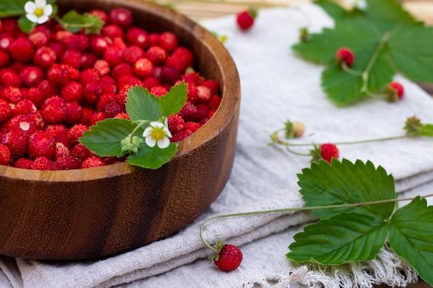 古い木の表面に赤い熟した野生のイチゴと花の木製ボウル