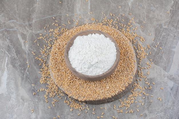 대리석 표면에 귀리 곡물과 나무 그릇