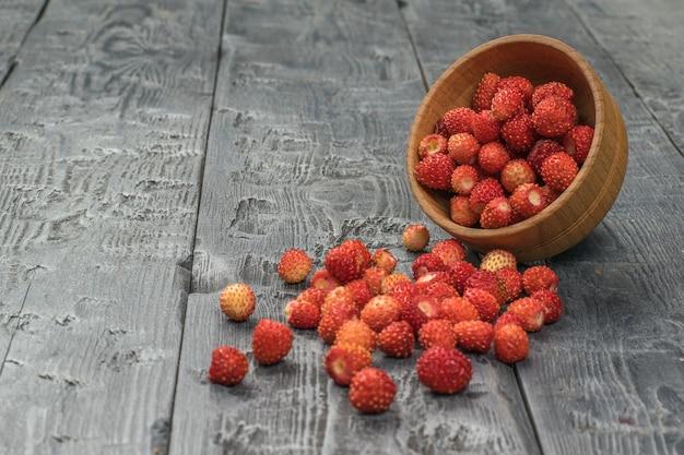 木製のテーブルの上に野生のイチゴが散らばっている木製のボウル。新鮮な作物。
