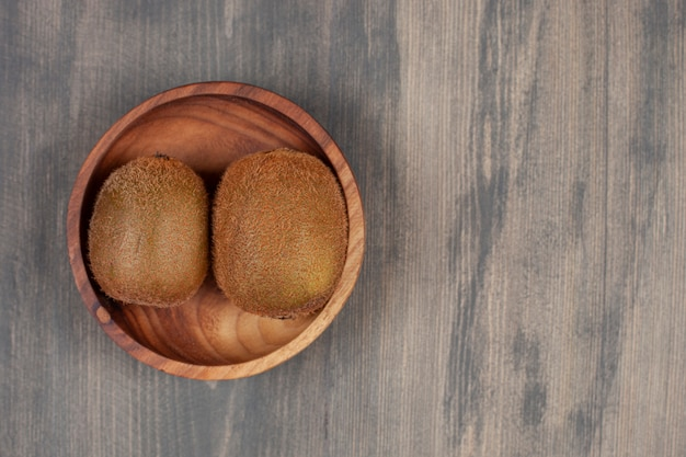 나무 테이블에 두 개의 신선한 키 위와 나무 그릇. 고품질 사진