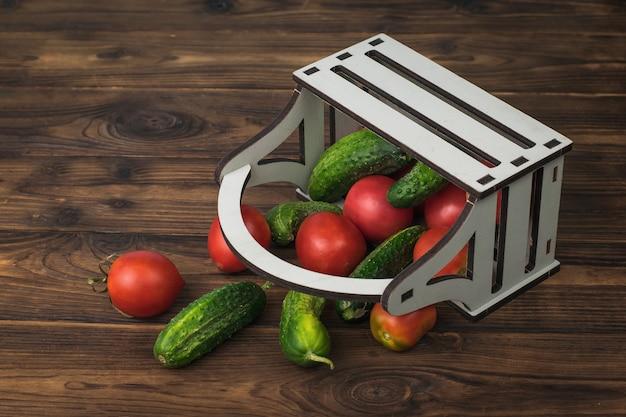 나무 테이블에 거꾸로 토마토와 오이가 있는 나무 상자. 야채의 신선한 작물입니다.