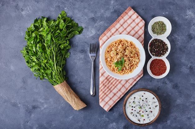 青いテーブルにパスタのプレートとヨーグルトスープの木製カップ。