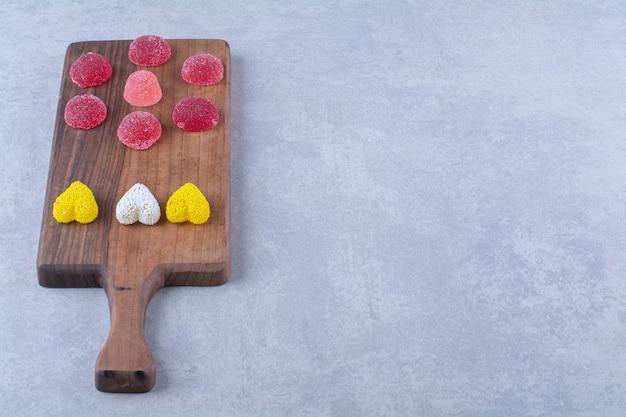 다채로운 설탕 젤리 캔디가 가득한 나무 도마. 고품질 사진