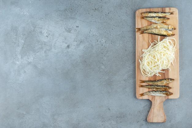 Деревянная разделочная доска, полная рыбы и сыра. фото высокого качества