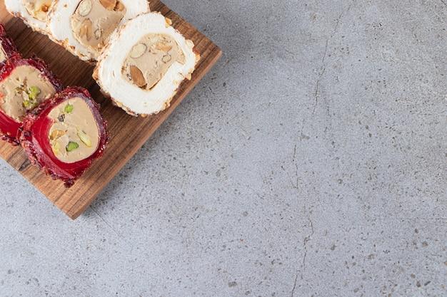 スライスされた伝統的なトルコの喜びでいっぱいの木製のまな板。