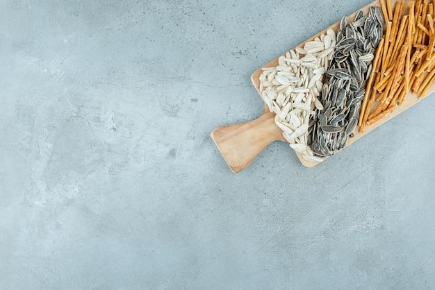 Деревянная разделочная доска, полная семечек и хлебных палочек. фото высокого качества