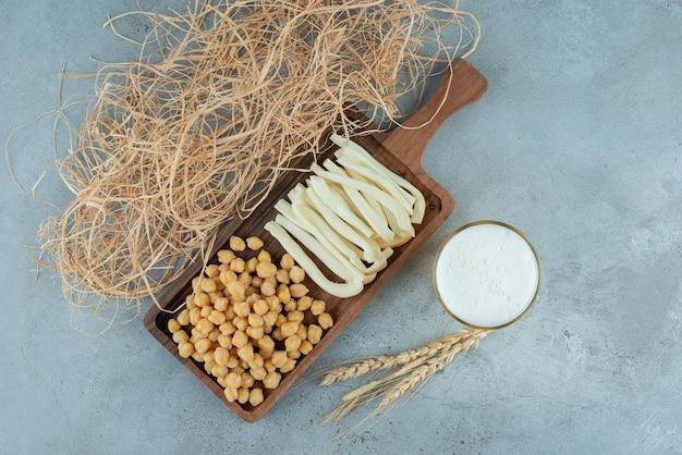 맥주 한 잔과 완두콩과 치즈의 나무 커팅 보드. 고품질 사진