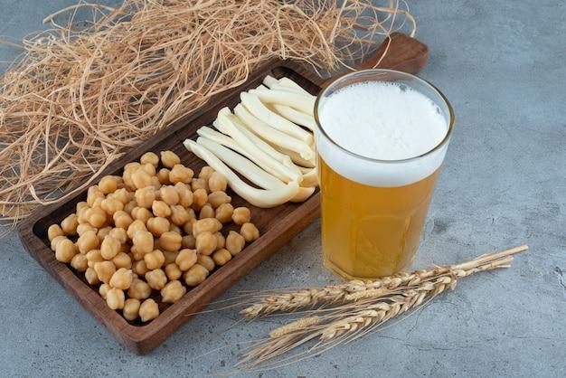 맥주 한 잔과 함께 완두콩과 치즈의 나무 커팅 보드. 고품질 사진