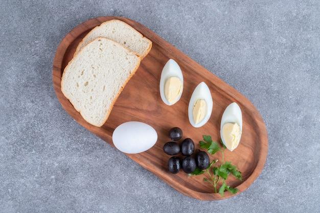 ゆで卵とパンのスライスが入った木製のまな板。高品質の写真