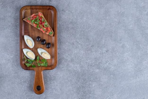 ゆで卵とトーストが入った木製のまな板。高品質の写真