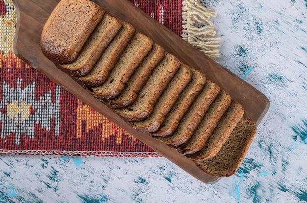 パンのスライスと木製のまな板。 無料写真