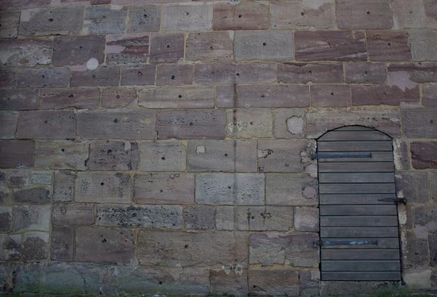 Деревянная дверь у каменной стены. прогулка возле замка