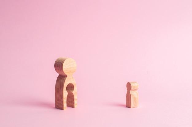 虫眼鏡の近くに女性と子供の木像が立っています。