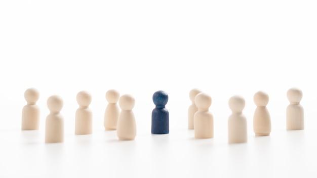 影響を与え、力を与えるためにチームと一緒に立っている木製の人物。リーダーシップの概念、成功した競争の勝者、そして新しい通常のライフスタイルのための影響力と社会的距離を持ったリーダー