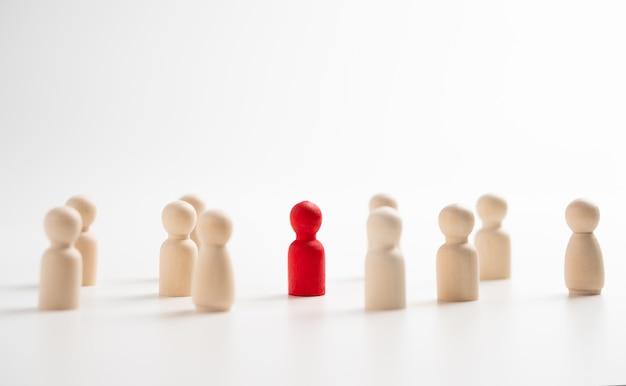 影響力とエンパワーメントのためにチームと一緒に立っている木製の人物。リーダーシップの概念、成功した競争の勝者、そして新しい通常のライフスタイルのための影響力と社会的距離を持ったリーダー
